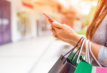 Foto de Woman holding shopping bags doing online shopping on her mobile phone in the supermarket. - Imagen libre de derechos