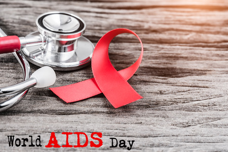 Photo pour Red ribbon awareness and stethoscope on wooden background  for World Aids day campaign. - image libre de droit