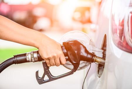 Photo pour Closeup of woman  hand holding a fuel pump at a station. - image libre de droit