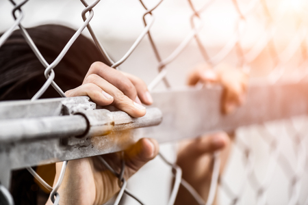 Photo pour Woman hand holding on chain link fence for remember Human Rights Day concept. - image libre de droit