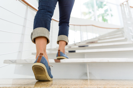 Photo for Young adult woman walking up the stairs with sun sport background. - Royalty Free Image