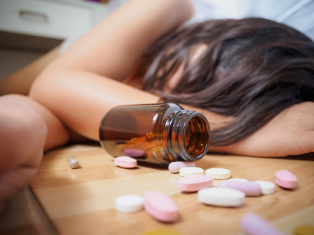 Foto de Young woman is lying on the floor with a lot of pills. Overdose and suicide concept. - Imagen libre de derechos