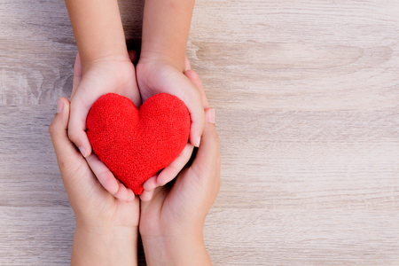 Foto de Health care, love, organ donation, family insurance and CSR concept. adult and child hands holding handmade red heart on wooden background. - Imagen libre de derechos