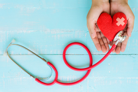 Photo pour World health day, Healthcare and medical concept. Woman hand holding red heart with Stethoscope, notepad or notebook, thermometer and yellow Pill on Pastel white and blue wooden table background texture. - image libre de droit