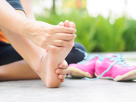 Photo pour Soft focus woman massaging her painful foot while exercising.   Running sport injury and healthcare concept. - image libre de droit