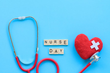 Foto de International Nurses Day, May 12. Healthcare and medical concept. Handmade Red heart with Stethoscope and Nurse day wooden block on blue background. - Imagen libre de derechos