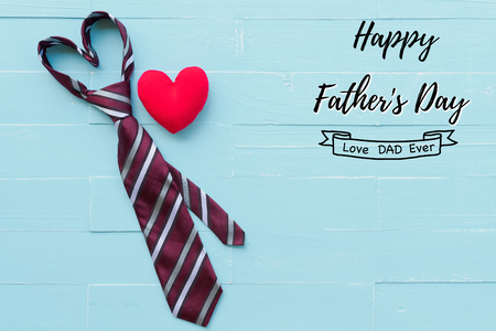 Photo pour Happy fathers day concept. Red tie in heart shape and handmade red heart on bright blue pastel wooden table background. - image libre de droit