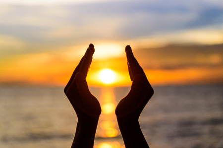 Foto de Woman hands holding the sun during sunrise or sunset. - Imagen libre de derechos