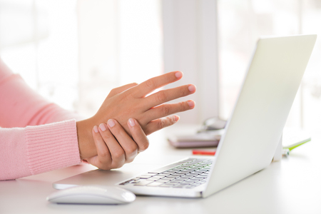 Foto per Closeup woman holding her wrist pain from using computer. Office syndrome hand pain by occupational disease. - Immagine Royalty Free