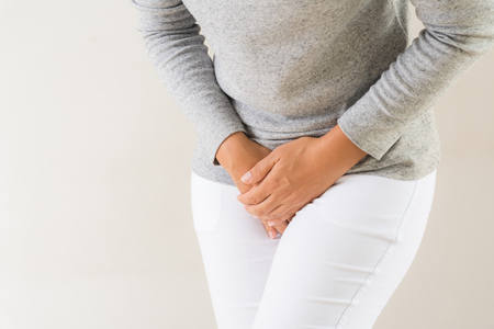 Foto de Young woman having painful stomachache with hands holding pressing her crotch lower abdomen. Medical or gynecological problems, healthcare concept - Imagen libre de derechos