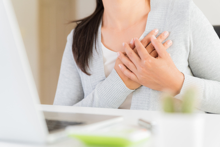 Foto de Closeup business woman having heart attack. Woman touching breast and having chest pain after long hours work on computer. Office syndrome, Healthcare And Medical concept. - Imagen libre de derechos