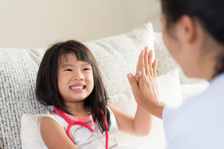 Photo for Happy little cute girl on consultation at the pediatrician. Girl is smiling and giving high five to doctor. Medicine and health care concept. - Royalty Free Image