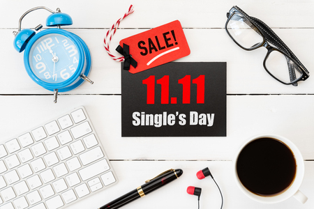 Foto de Online shopping of China, 11.11 single day sale concept. Red and black ticket with coffee cup, keyboard computer and mouse on white wooden background. Shopping concept. - Imagen libre de derechos