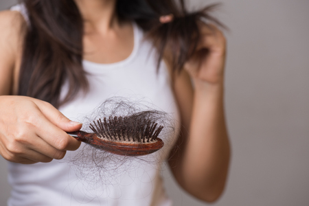 Foto de Healthy concept. Woman show her brush with long loss hair and looking at her hair. - Imagen libre de derechos