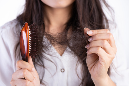 Foto de Healthy concept. Woman show her brush with damaged long loss hair and looking at her hair. - Imagen libre de derechos