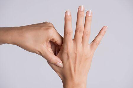 Foto de Healthcare and medical concept. Woman massaging her painful hand. - Imagen libre de derechos