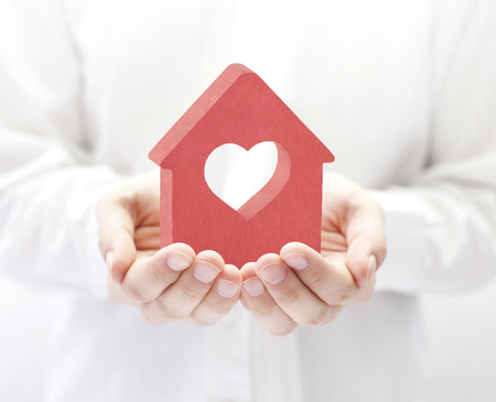 Foto de Small house with heart in hands - Imagen libre de derechos