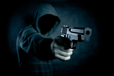 Foto de Hooded man with a gun in the dark - Imagen libre de derechos