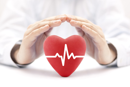 Foto de Heart pulse covered by hands. Health insurance concept - Imagen libre de derechos