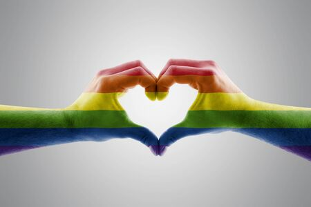Photo pour Two hands in the form of LGBT rainbow heart symbol of love - image libre de droit