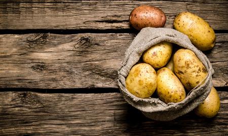 Foto de Fresh potatoes in an old sack on wooden background - Imagen libre de derechos