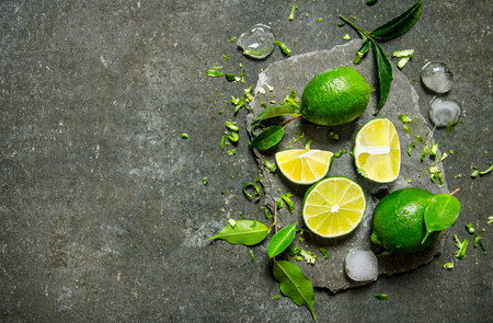 Foto de Slices of lime with ice and leaves on a stone stand On the stone table. - Imagen libre de derechos