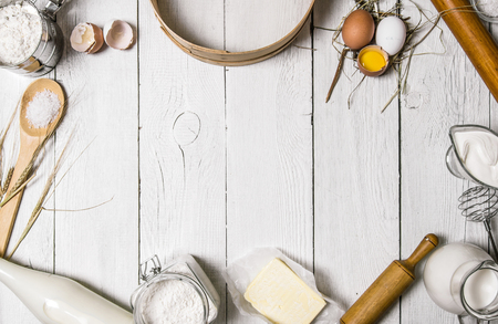 Foto per Baking background. Ingredients for the dough - Milk, eggs, flour, sour cream, butter, salt and different tools. On a white wooden background. Free space for text . Top view - Immagine Royalty Free