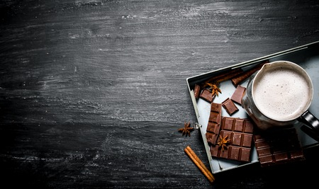 Photo for Hot chocolate with cinnamon and bitter chocolate. On black rustic background. - Royalty Free Image