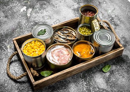Foto de Various canned products in tin cans on a wooden tray. On a rustic background. - Imagen libre de derechos