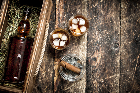 Foto de Whiskey background. A bottle of whiskey in an old box with glasses and a cigar. On a wooden background. - Imagen libre de derechos