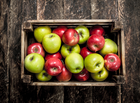 Photo for box with fresh red and green apples. On a wooden background. - Royalty Free Image