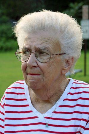 Portrait of worried senior citizen woman at a park.