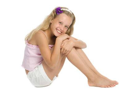 Pretty teenage girl sit on floor isolated on white