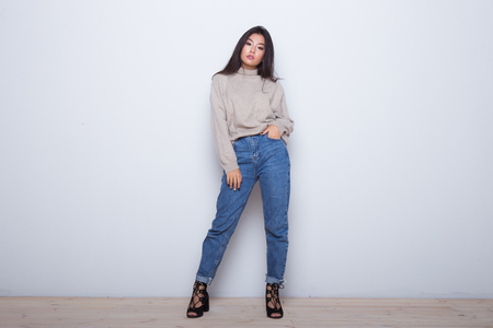 Photo pour Fashion posing beautiful Asian girl in trendy wearing. Casual wearing in jeans, high heel shoes and sweeter - image libre de droit