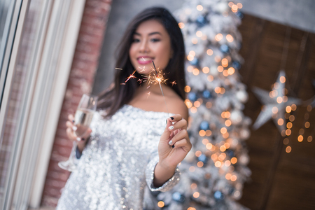 Photo for Beautiful girl with a fireworks in her hand dancing on the club, fun and waiting for Christmas time. Ready to celebrate. Confetti and fireworks. Christmas party - Royalty Free Image