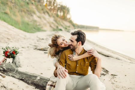 Photo for A young couple is smiling and hugging on the beach. Beautiful girl embrace her boyfriend from back. Wedding walk. Artwork - Royalty Free Image