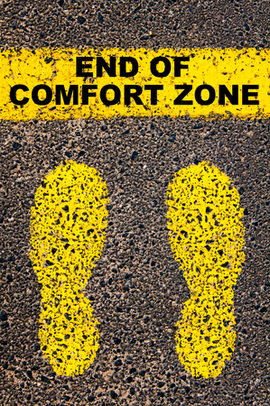 Photo pour End of Comfort Zone message. Conceptual image with yellow paint footsteps on the road in front of horizontal line over asphalt stone background. - image libre de droit