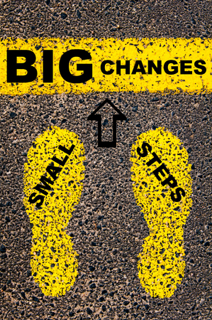Photo pour Small Steps Big Changes Message. Conceptual image with yellow paint footsteps on the road in front of horizontal line over asphalt stone background. - image libre de droit