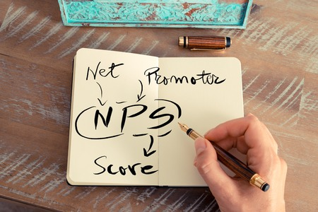 Foto de Retro effect and toned image of a woman hand writing a note with a fountain pen on a notebook. Handwritten text NPS NET PROMOTER SCORE, business success concept - Imagen libre de derechos