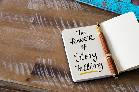 Foto de Retro effect and toned image of notebook next to a fountain pen. Business concept image with handwritten text THE POWER OF STORY TELLING , copy space available - Imagen libre de derechos