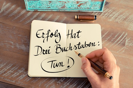 Retro effect and toned image of woman hand writing a note on a notebook. Handwritten text in German  Erfolg Hat Drei Buchstaben: Tun! - translation : Success Has Three Letters: Do, concept image