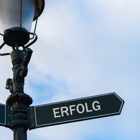 Street lighting pole with conceptual message Erfolg translation Success in German on directional arrow over blue cloudy background.