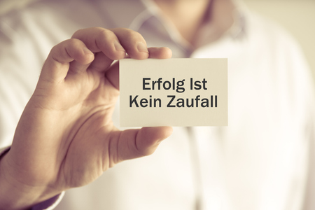 Closeup on businessman holding message card Erfolg Ist Kein Zaufall written in German - translation : Success Is Not An Accident, business concept image with soft focus background and vintage tone