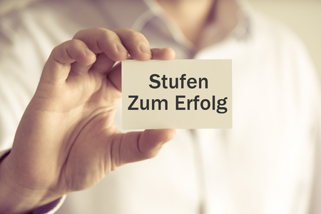 Closeup on businessman holding message card Stufen Zum Erfolg written in German - translation : Steps To Success, business concept image with soft focus background and vintage tone