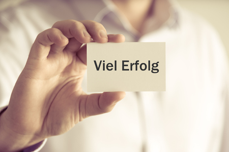 Closeup on businessman holding message card Viel Erfolg written in German - translation : Much Success, business concept image with soft focus background and vintage tone