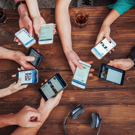 Foto de Top view hands circle using phone in cafe - Multiracial friends mobile addicted interior scene from above - Wifi connected people in bar table meeting - Concept of teamwork - Imagen libre de derechos