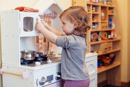 Photo for toddler girl playing toy kitchen - Royalty Free Image