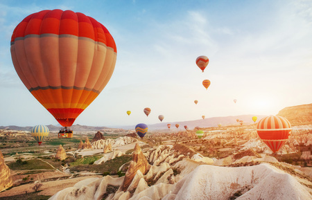 Photo for Hot air balloon flying over rock landscape at Turkey. Cappadocia with its valley, ravine, hills, located between the volcanic mountains in Goreme National Park. - Royalty Free Image