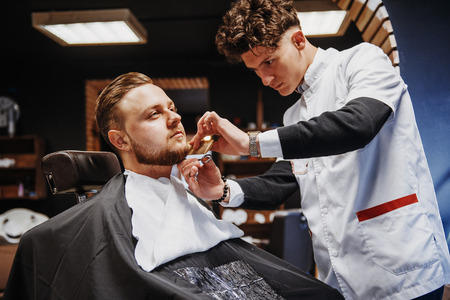 Photo pour Mens hairstyling and haircutting in a barber shop or hair salon. - image libre de droit