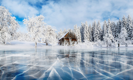 Foto de Blue ice and cracks on the surface of the ice. Frozen lake under a blue sky in the winter. Cabin in the mountains. Mysterious fog. Carpathians. Ukraine, Europe. - Imagen libre de derechos